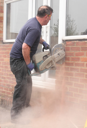 A window fitter using a disc cutter on brickwork to widen an opening for the installation of new French doors and windows being fitted