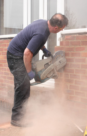 A window fitter using a disc cutter on brickwork to widen an opening for the installation of new French doors and windows being fitted photo