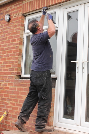 A window fitter preparing for the fitting of new plastic doors and windows to a bungalow photo