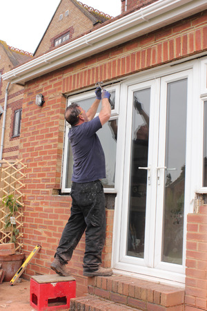 installation: A window fitter preparing for the fitting of new pastic doors and windows to a bungalow Stock Photo