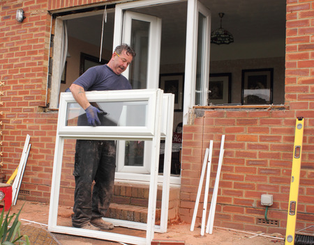 fitting: A window fitter renewing plastic doors and windows to a bungalow Stock Photo