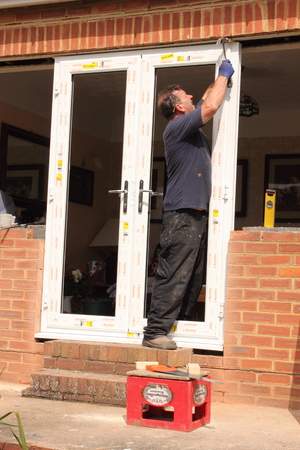 A window fitter renewing plastic doors and windows to a bungalow, may 2014 Editorial