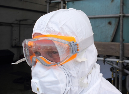 regulated: Industrial Cleaner wearing his full ppe for a steam boiler clean