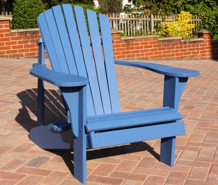 A handmade Adirondack style chair made out of old recycled wood painted blue