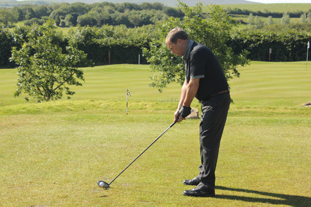 A golfer ready to hit the golfball down the fairway  photo