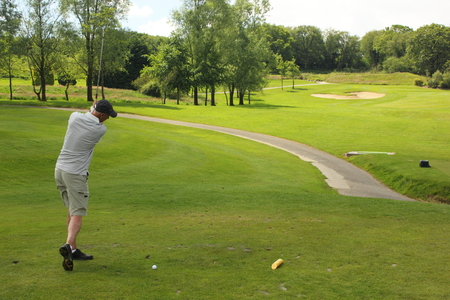 A golfer hitting the golfball down the fairway  photo