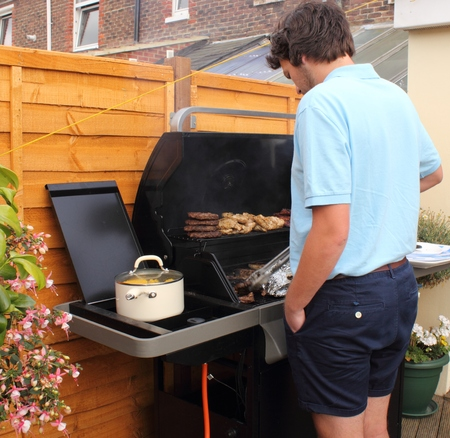 A young man cooking on the bbq during the summer sunshine photo