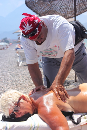 Masseur giving a full massage to a beautiful mature woman on the beach at calis in Turkey on the 19th july 2014