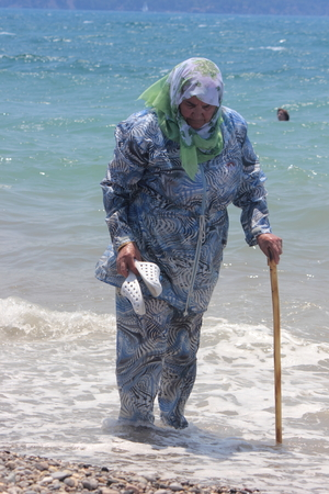 An old Turkish lady in traditional clothing on the beach at calis in Turkey,19th july 2014
