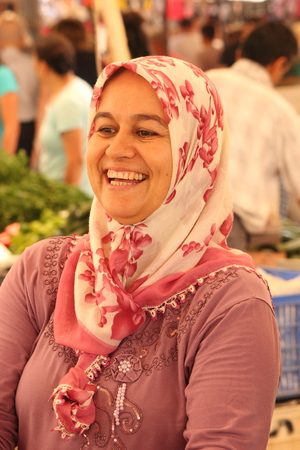 CALIS, TURKEY - 20TH JULY, 2014  A turkish lady with a beautiful smile selling her fresh fruits and vegetables at a local produce market in Calis, Turkey 20th july 2014