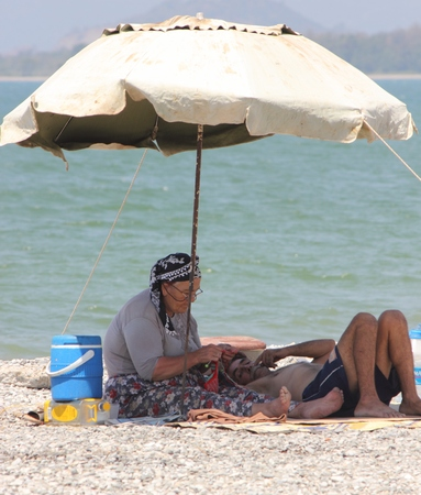 An old turkish couple on the beach with umbrella for shade at calis in turkey, 2014