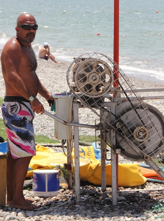 turkish man: The fethiye surf center,a turkish man operating the pully equipment for learners learning how to kitesurf at calis beach in turkey, 2014