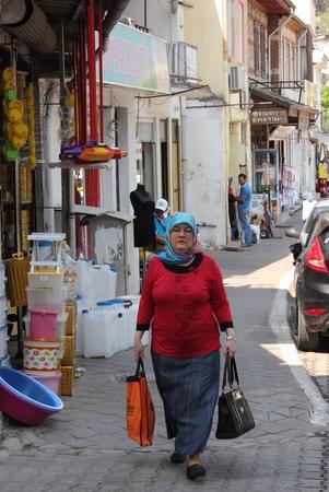 A turkish lady walking along a street after shopping in fethiye, turkey 2014