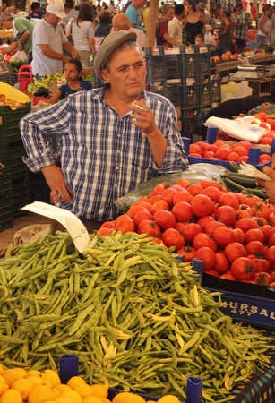 turkish man: A retro turkish man wearing a flat cap and smoking while selling his vegetables at a market in calis in turkey,july 2014