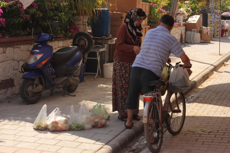 A turkish couple using a bicycle to get their purchases from the local market home, calis, turkey 2014