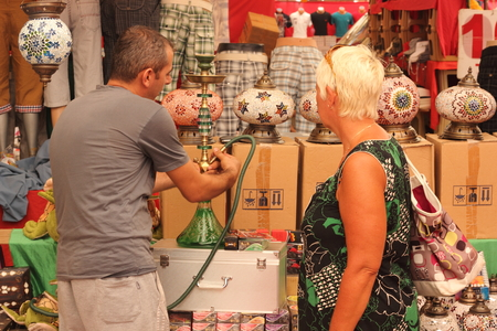 turkish man: An english lady buying a hookah water pipe from a turkish man at a market in calis in turkey ,july 2014 Editorial