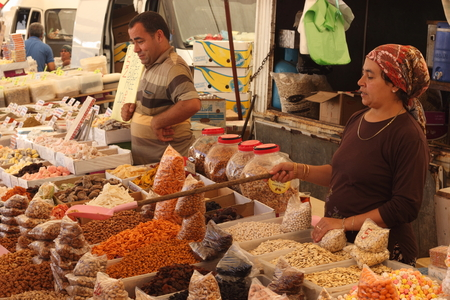 CALIS, TURKEY - 20TH JULY, 2014 A turkish lady selling her fresh spices and nuts at a local produce market in Calis, Turkey 20th july 2014