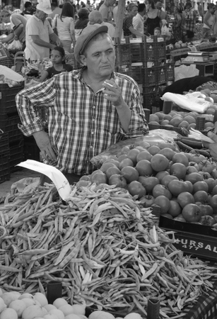 A retro turkish man wearing a flat cap and smoking while selling his vegetables at a market in calis in turkey,july 2014