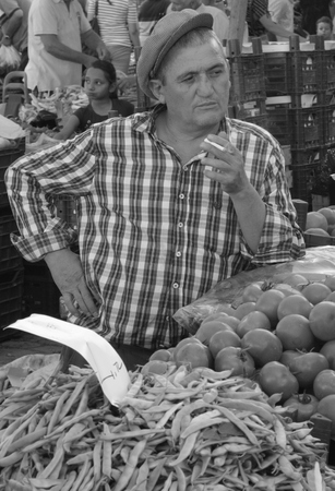 b w: A retro turkish man wearing a flat cap and smoking while selling his vegetables at a market in calis in turkey,july 2014