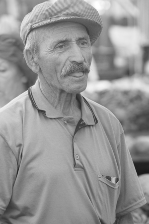 An old turkish male wearing a hat in black and white
