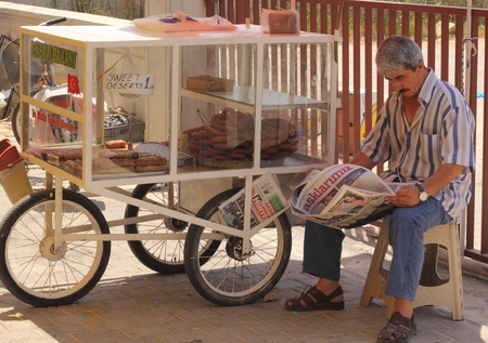 turkish man: An old turkish man reading the paper while selling his pastries from a cart at a local market in calis, turkey 2014