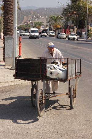 turkish man: An old turkish man pushing his three wheeled cart through the streets of calis in turkey, 2014