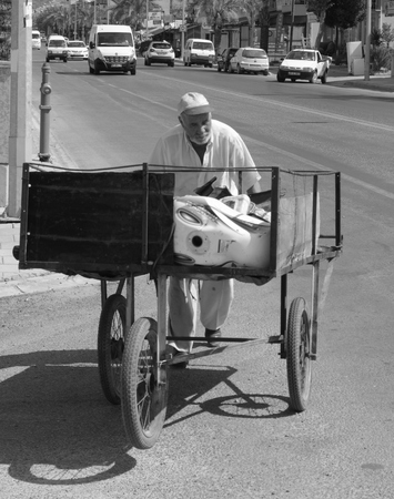 An old turkish man pushing his three wheeled cart through the streets of calis in turkey, 2014