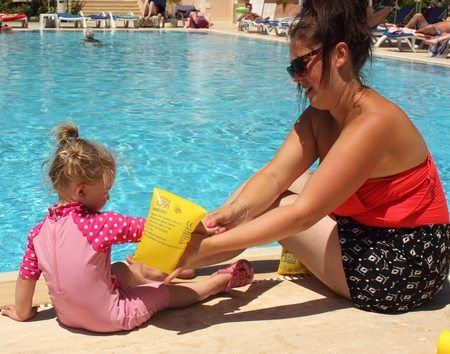 A mother putting armbands on her young daughter before she goes into the swimming pool while on vacation