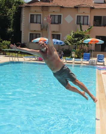 englishman: An englishman jumping into a swimming pool while on vacation Editorial