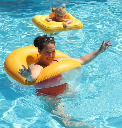 A mother with her young daughter with floatation aids in a swimming pool photo