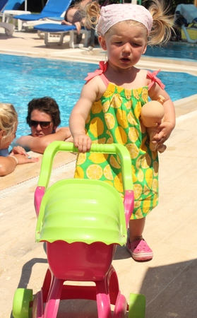 A young girl with her baby doll and pram while on holiday photo
