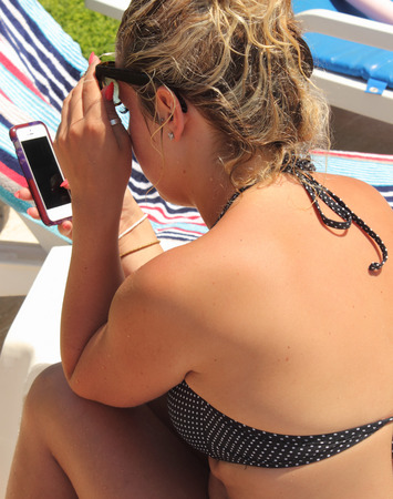 lady on phone: A young lady using her phone at the beach Stock Photo