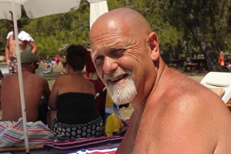 englishman: An englishman with a bald head and a beard on a beach Stock Photo