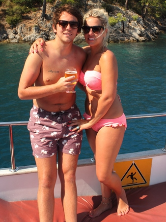 A young couple wearing swimwear and having a drink while on vacation, 2014 photo