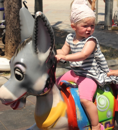 A young girl on a donkey playground ride photo