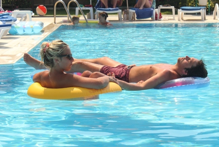 A young couple relaxing in a swimming pool while on vacation,2014 Stock Photo