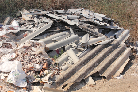 Asbestos waste dumped on open land