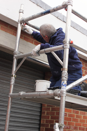 A painter working from a scaffold tower photo