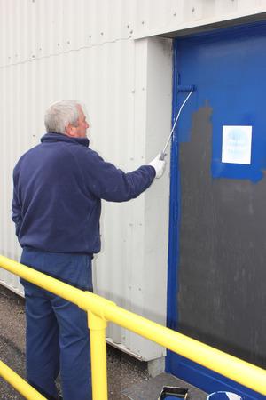 A painter painting a door using a gloss roller photo