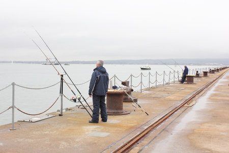 Two fishermen sea fishing from a jetty photo