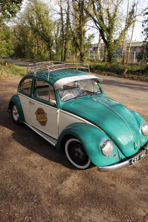 vw: A 50 year old retro vw beetle car fitted with a sunvisor and has been lowered, in portsmouth england, 12th april 2015