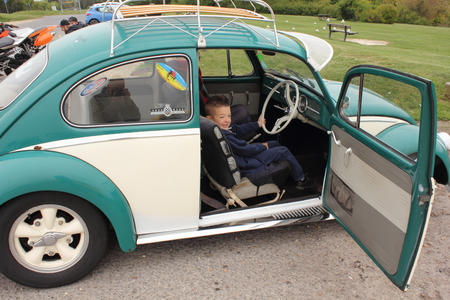 vw: A young boy in a classic old vw beetle car, 2015 Editorial