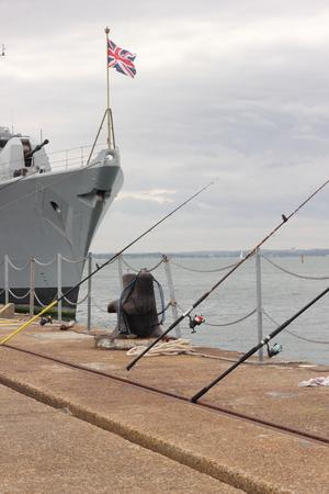 alongside: Fishing alongside a british warship in a dockyard Stock Photo