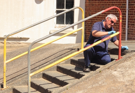 topcoat: A painter painting handrails along a walkway with concrete steps