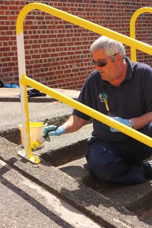 concrete steps: A painter painting handrails along a walkway with concrete steps