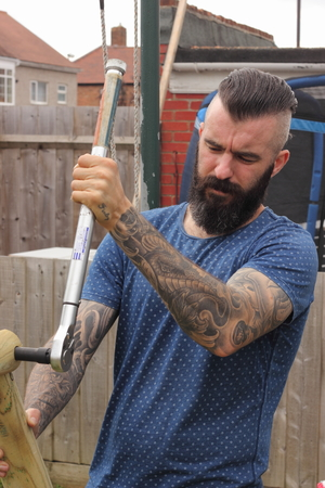 torque: A man building a childrens wooden swing and using a torque wrench in a garden Stock Photo