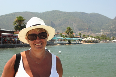 fethiye: An english lady wearing a hat for shade while on vacation at fethiye in turkey, 2015