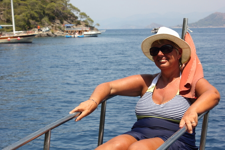 fethiye: An english lady relaxing while on a boat trip around the bays at fethiye in turkey, 2015 Stock Photo
