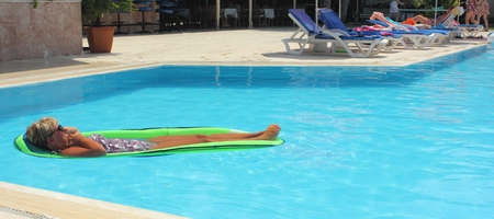 lilo: An english Lady relaxing in a swimming pool while on holiday