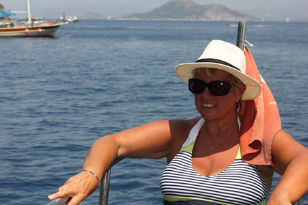 adulthood: An english lady relaxing while on a boat trip around the bays at fethiye in turkey, 2015 Stock Photo